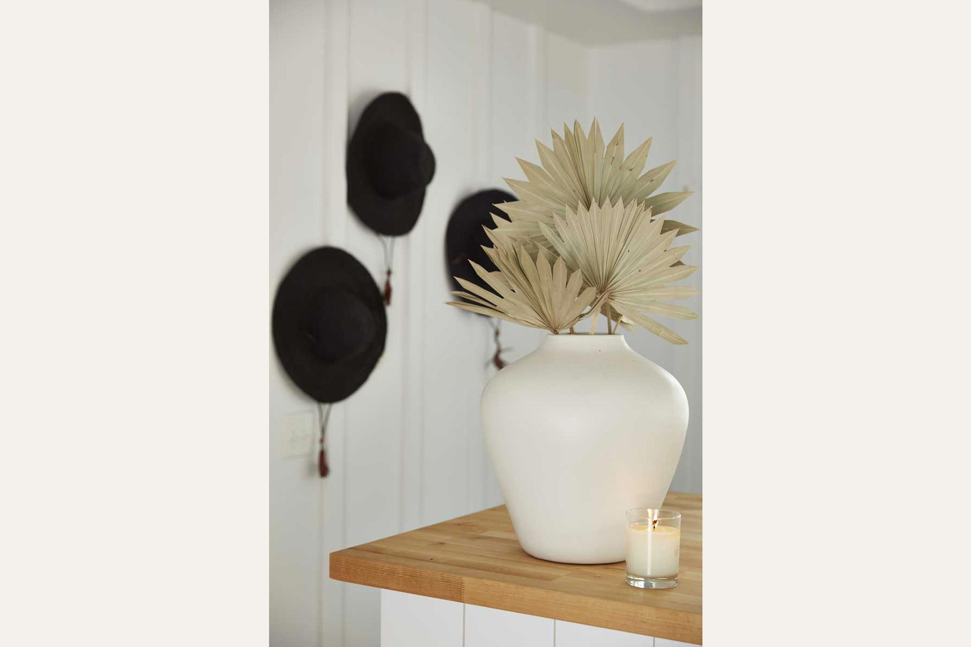 black sun hats hanging in front of vase